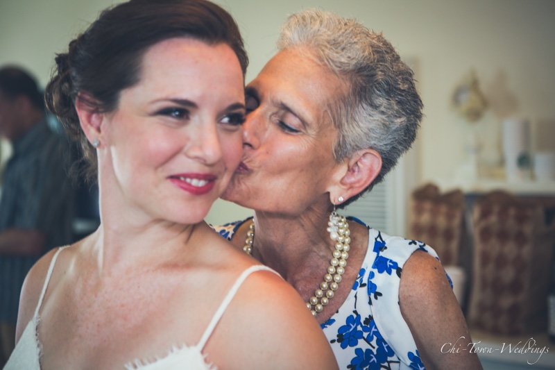 Candid mom kissing bride on cheek