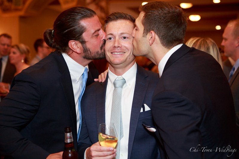 Groom being kissed on cheeks by Groomsmen candid