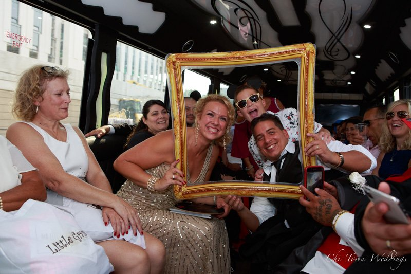 Candid Wedding Party using a frame to pose on bus