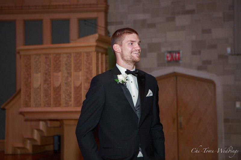 Groom candidly smiling when he sees bride for 1st time